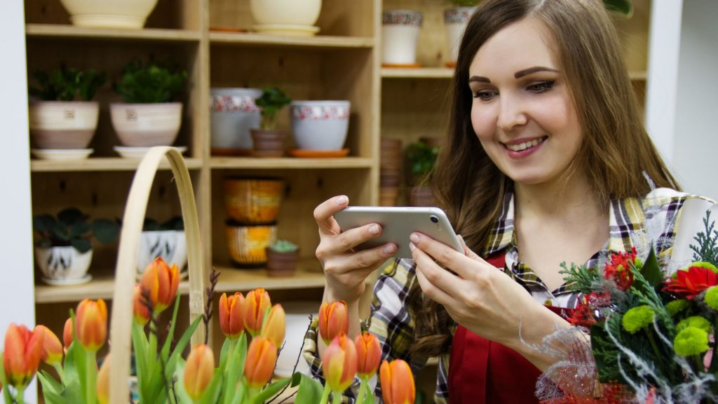 Businesswoman filming plants on smartphone - This Is How Small Businesses Are Using Video Marketing In 2020